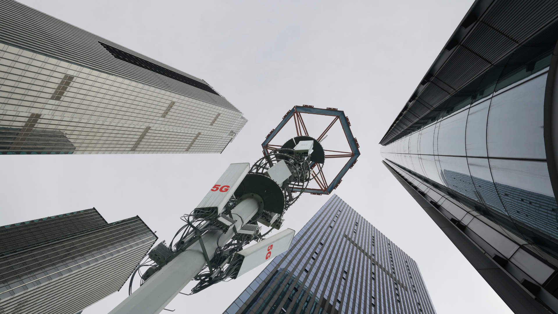5G transmission tower in downtown with corporate buildings
