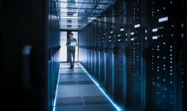 Telecom professional running diagnostics and maintenance in big data centre full of data servers