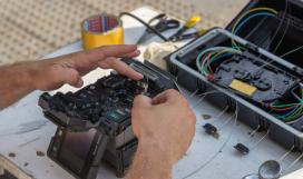 Fibre optic technician using a fusion splicer to connect fibre optic cables